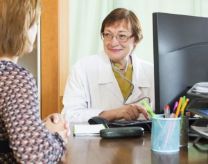 Mature doctor behind computer with patient